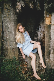 Jong aantrekkelijk blootsvoets blondemeisje in blauwe romantische kledingszitting in de oude boom