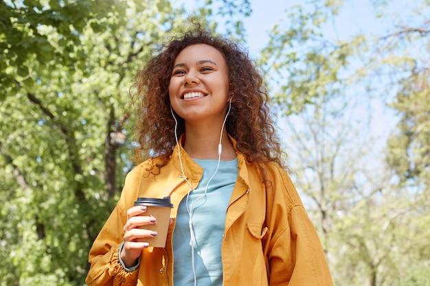 Jong aantrekkelijk donkerhuidig krullend meisje dat breed lacht, een geel jasje draagt, een kopje koffie vasthoudt, in het park loopt, naar muziek luistert en geniet van het weer.