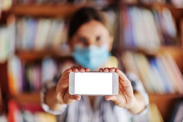 Jong aantrekkelijk eerstejaarsmeisje dat met gezichtsmasker slimme telefoon met wit scherm houdt. studeren tijdens covid pandemie concept.
