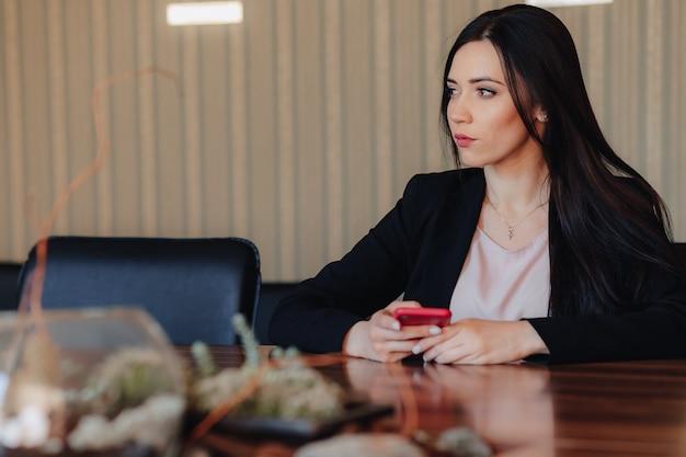 Jong aantrekkelijk emotioneel meisje die in bedrijfsstijlkleren bij bureau met telefoon in bureau of publiek zitten