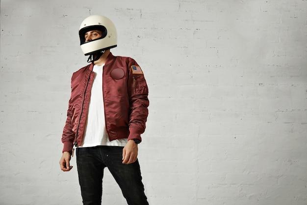 Jong aantrekkelijk mannelijk model in zwarte spijkerbroek, effen wit t-shirt, bordeauxrood nylon bomberjack en een witte motorhelm