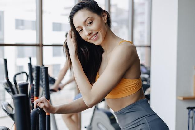 Jong aantrekkelijk meisje bij gymnastiek op hometrainer, fitness en yoga
