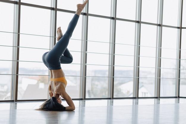 Jong aantrekkelijk meisje dat geschiktheidsoefeningen met yoga op de vloer doet. panoramische ramen