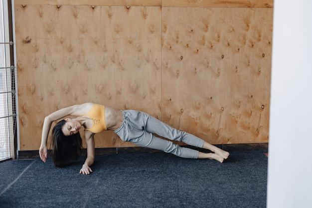 Jong aantrekkelijk meisje dat geschiktheidsoefeningen met yoga op de vloer doet