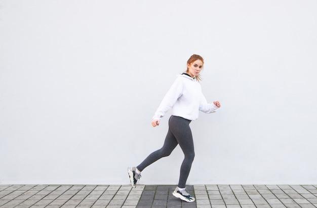 Jong aantrekkelijk meisje dat sportkleding draagt die op een witte achtergrond loopt, copyspace