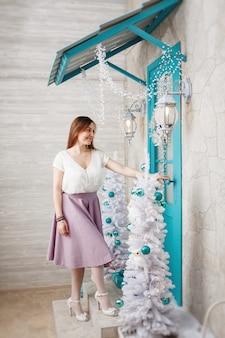 Jong aantrekkelijk meisje opent de deur naar het huis ingericht voor het nieuwe jaar.