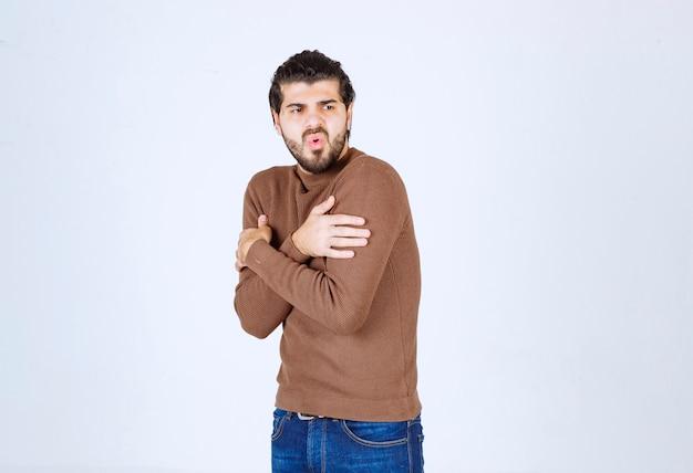 Jong aantrekkelijk model in bruine trui die gebaren over witte muur doet.