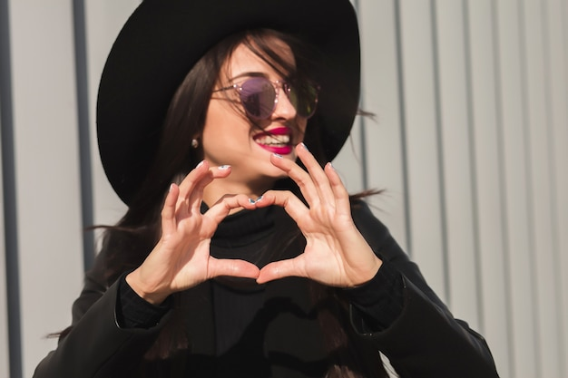 Jong aantrekkelijk model in zwarte hoed en zonnebril met hartvormige handen, poserend op straat