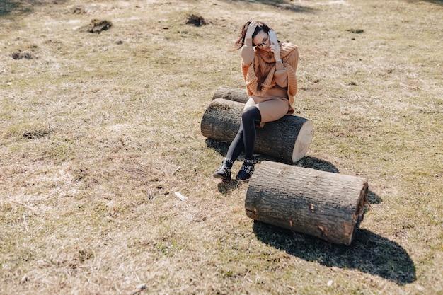 Jong aantrekkelijk modieus meisje op aard op bosmuur met telefoon op een zonnige dag. outdoor vakanties en afhankelijkheid van technologie.
