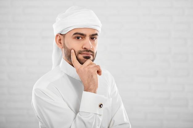 Jong aantrekkelijk moslimmannetje in traditionele islamitische cloting die over iets denkt