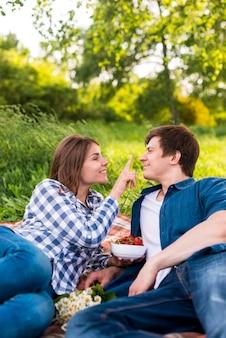 Jong aantrekkelijk paar dat van datum op deken geniet