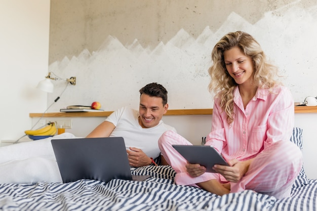 Jong aantrekkelijk paar zittend op bed in de ochtend, nieuws lezen op internet, online freelancer baan