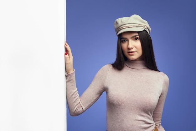Jong aantrekkelijk schattig meisje dat zich naast een lege witte aanplakbordmuur bevindt