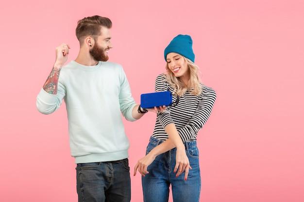 Jong aantrekkelijk stel dat naar muziek luistert op een draadloze luidspreker met een coole stijlvolle outfit die lacht, een vrolijke positieve stemming die zich voordeed op roze