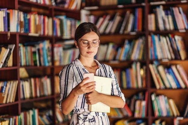 Jong aantrekkelijk universiteitsmeisje dat zich in bibliotheek bevindt, een boek houdt en slimme telefoon met behulp van.