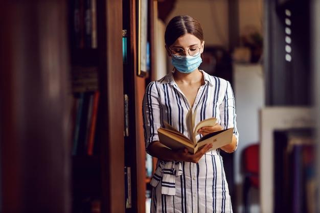 Jong aantrekkelijk universiteitsmeisje met gezichtsmasker bij het staan in bibliotheek en het bladeren door materiaal in een boek voor schoolproject tijdens coronaviruspandemie.