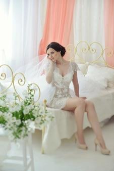 Jong aantrekkelijk vrouwelijk modelmeisje vóór de huwelijkszitting op het bed.