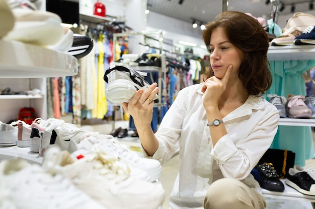 Jong aantrekkelijk vrouwelijk ogen musingly paar schoenen in winkelcentrum