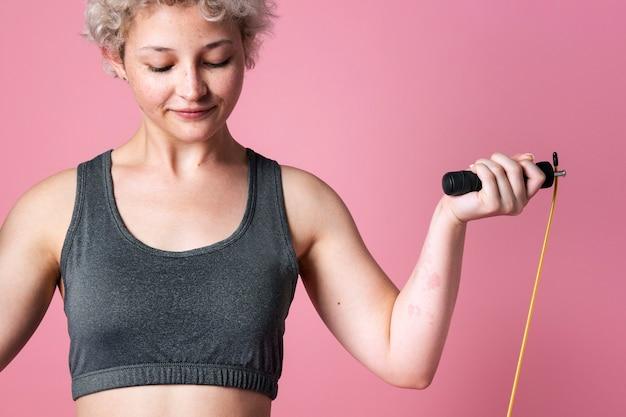 Jong actief meisje met een springtouw voor cardiotraining in een roze studio als achtergrond