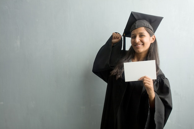 Jong afgestudeerd indiase vrouw tegen een muur erg blij en opgewonden, het verhogen van de armen