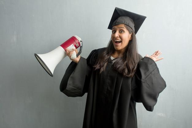 Jong afgestudeerd indiase vrouw tegen een muur gek en wanhopig, schreeuwen uit de hand