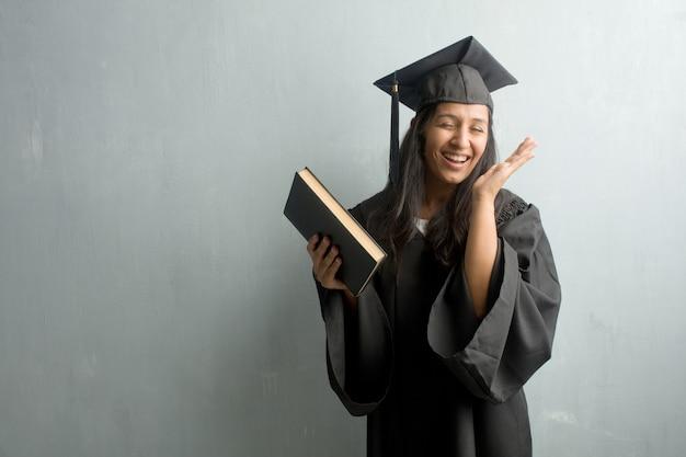 Jong afgestudeerd indiase vrouw tegen een muur lachen en plezier hebben, ontspannen en che