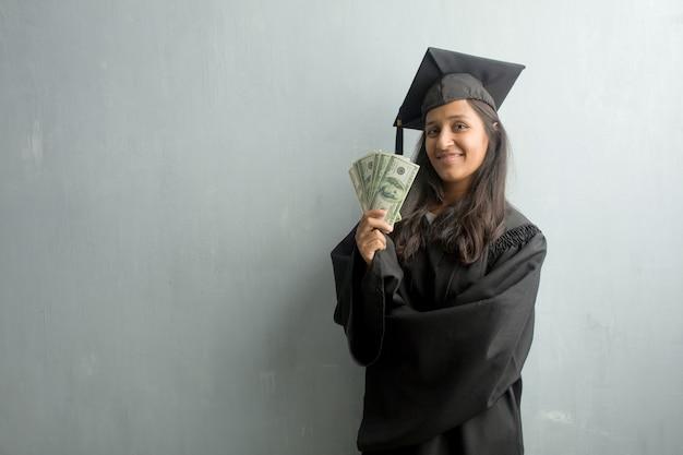 Jong afgestudeerd indiase vrouw tegen een muur met de handen op de heupen, staan, ontspannen en smil