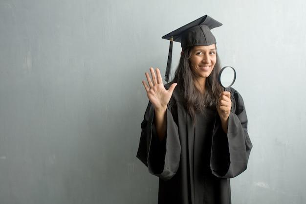 Jong afgestudeerd indiase vrouw tegen een muur met nummer vijf, symbool van het tellen, concept van wiskunde, zelfverzekerd en vrolijk. een vergrootglas vasthouden.