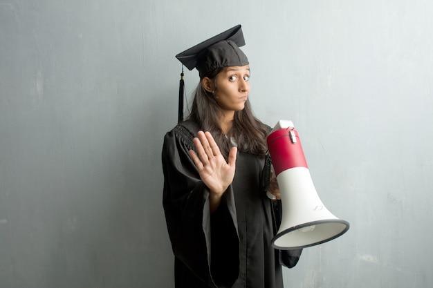 Jong afgestudeerd indiase vrouw tegen een muur moe en verveeld