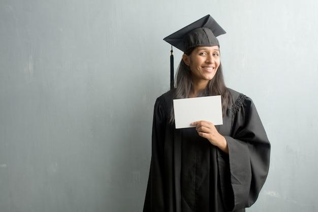 Jong afgestudeerd indiase vrouw tegen een muur vrolijk en met een grote glimlach, zelfverzekerd, vriendelijk en oprecht