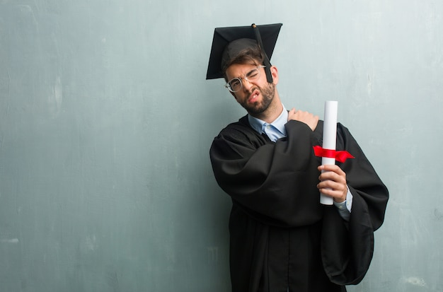 Jong afgestudeerd man tegen een grunge muur met een kopie ruimte met pijn in de rug als gevolg van het werk str