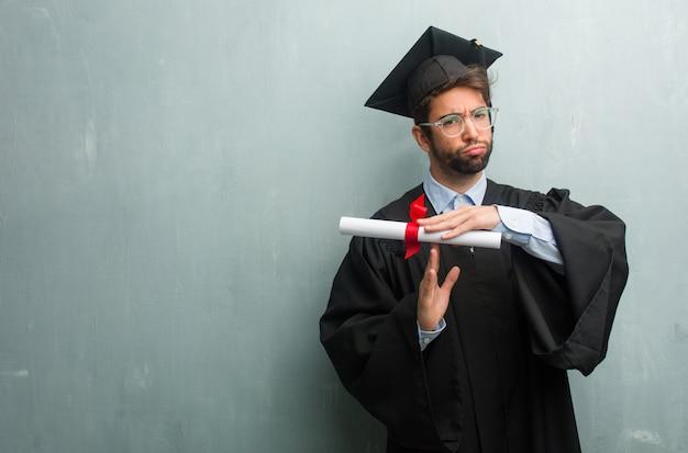Jong afgestudeerd man tegen een grunge muur met een kopie ruimte moe en verveeld