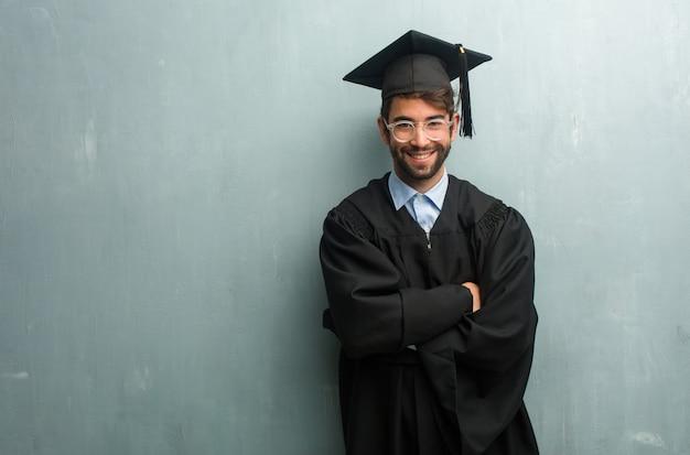 Jong afgestudeerd man tegen een grunge muur met een kopie ruimte overschrijding van zijn armen