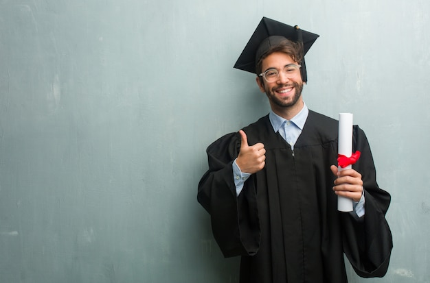 Jong afgestudeerd man tegen een grunge muur met een kopie ruimte vrolijk en opgewonden