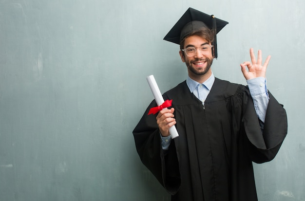 Jong afgestudeerd man tegen een grunge muur met een kopie ruimte vrolijk en vol vertrouwen doen ok gebaar