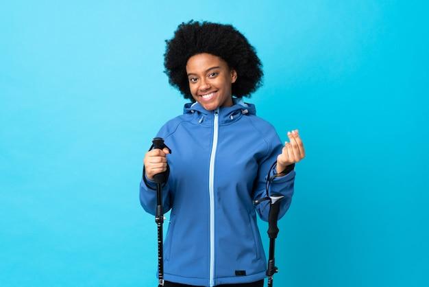 Jong afrika amerikaan met rugzak en trekkingstokken die op blauwe muur worden geïsoleerd die geldgebaar maken