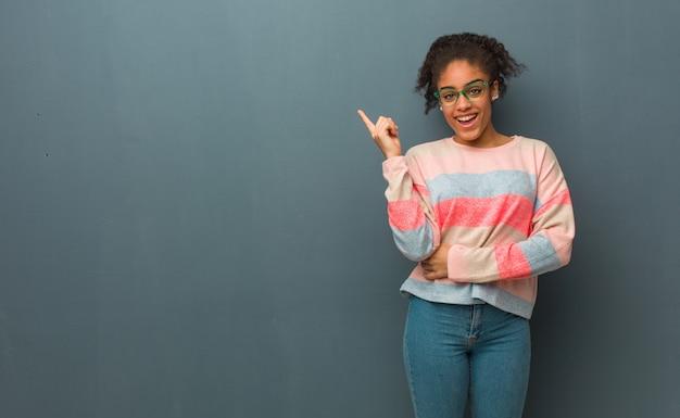 Jong afrikaans amerikaans meisje dat met blauwe ogen aan de kant met vinger richt