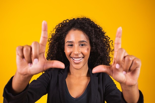 Jong afrikaans amerikaans meisje dat uitvoerende kleding draagt die lacht en fotolijstjes maakt met handen en vingers met een blij gezicht. creativiteit en fotografie concept.