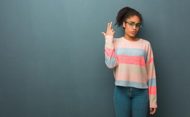 Jong afrikaans amerikaans meisje met blauwe ogen die een zelfmoordgebaar doen