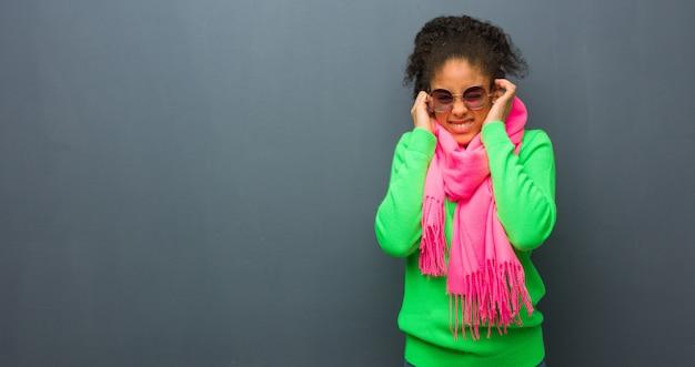 Jong afrikaans amerikaans meisje met blauwe ogen die oren behandelen met handen