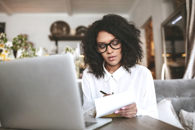 Jong afrikaans amerikaans meisje met glazen die in restaurant zitten en notities schrijven. mooi meisje met donker krullend haar, werken in café met laptop