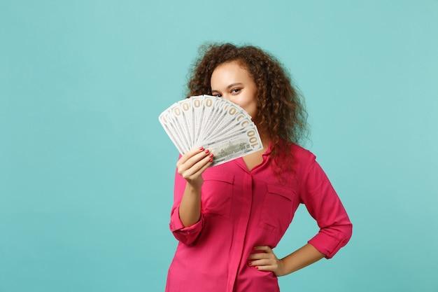 Jong afrikaans meisje die gezicht behandelen met ventilator van geld in dollarbankbiljetten, contant geld dat op blauwe turkooizen muurachtergrond in studio wordt geïsoleerd. mensen oprechte emoties, lifestyle concept. bespotten kopie ruimte.