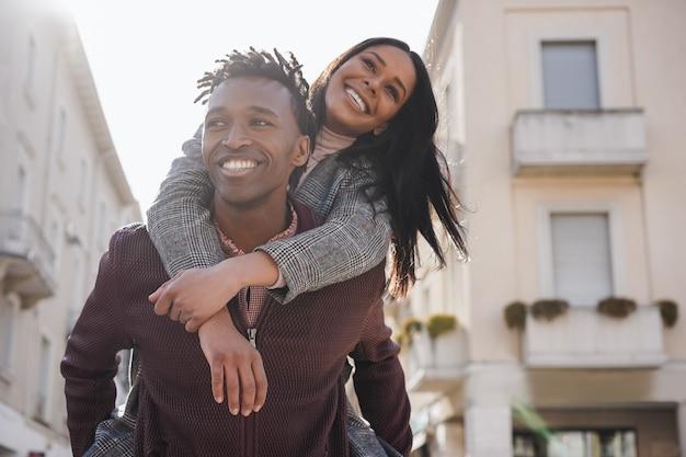 Jong afrikaans stel dat plezier heeft in het wandelen door de stad - focus op het gezicht van de man