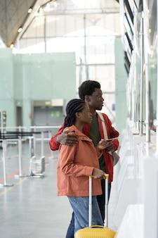 Jong afrikaans stel op luchthaven bij incheckbalie na covid einde eerste reis na coronavirus