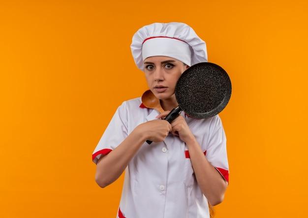 Jong angstig kaukasisch kokmeisje in eenvormige chef-kok houdt en kijkt door koekenpan en houten lepel die op oranje achtergrond met exemplaarruimte wordt geïsoleerd