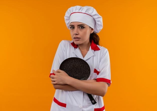 Jong angstig kaukasisch kokmeisje in eenvormige chef-kok houdt koekenpan met wapens die op oranje achtergrond met exemplaarruimte worden geïsoleerd