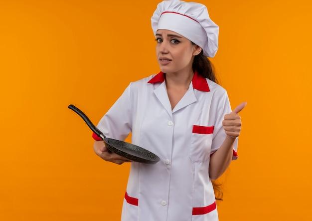 Jong angstig kaukasisch kokmeisje in uniform chef-kok houdt koekenpan en duimen omhoog geïsoleerd op een oranje achtergrond met kopie ruimte