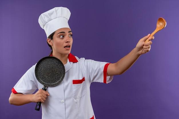Jong angstig kaukasisch kokmeisje in uniform chef-kok houdt koekenpan en wijst naar de kant met houten lepel geïsoleerd op violette achtergrond met kopie ruimte