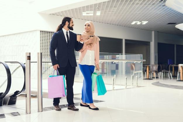 Jong arabisch paar dat in modern wandelgalerij winkelt.