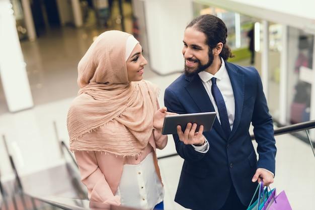 Jong arabisch paar dat in wandelgalerij winkelt.